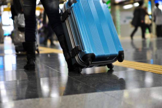 青いスーツケースを引いて歩く人