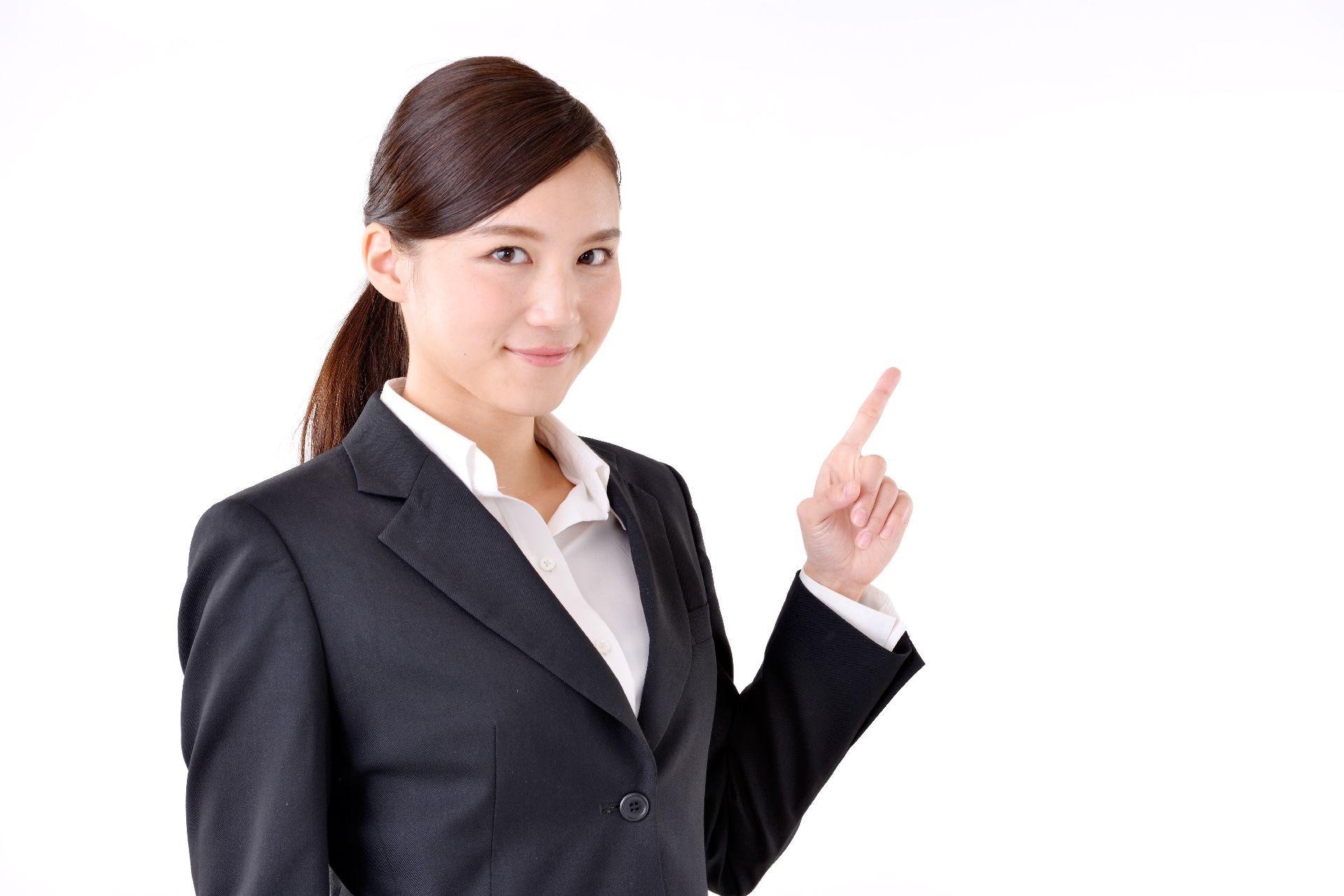 人差し指を立てたスーツの女性