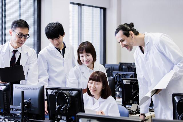 パソコンの画面を見る白衣の学生たち