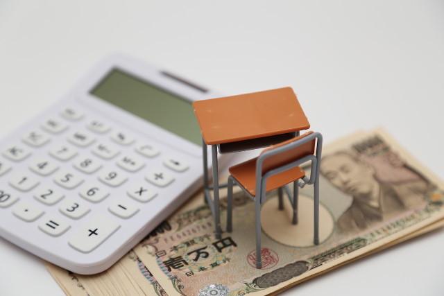 お札の上に置かれたミニチュアの学校机と電卓