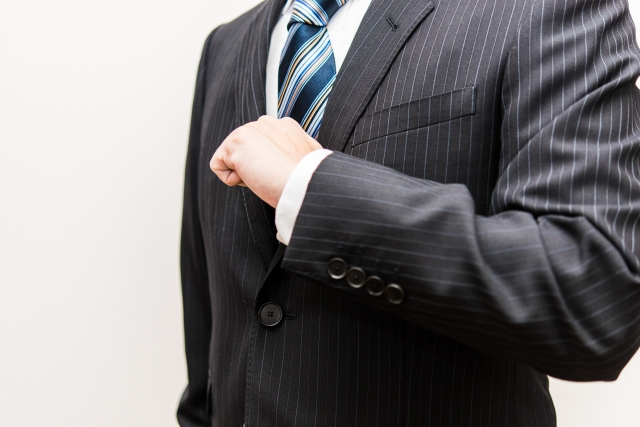 拳を胸にあてるスーツの男性