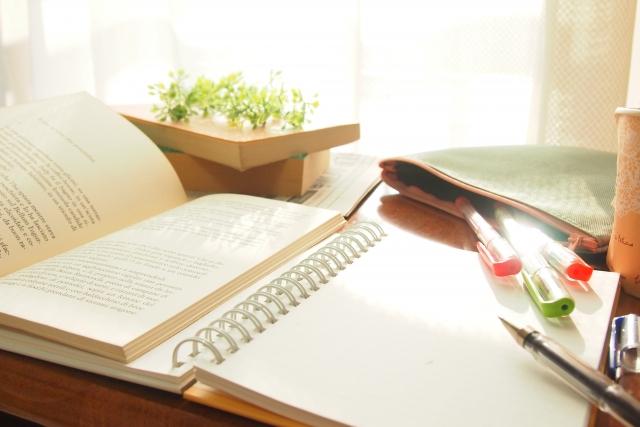 机に広げられた本とノート