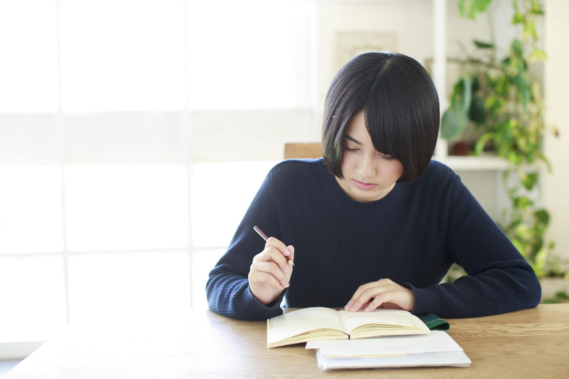 本を読みながら問題を解く女性