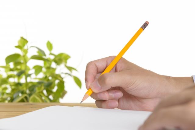 机に向かって小論文を書く人