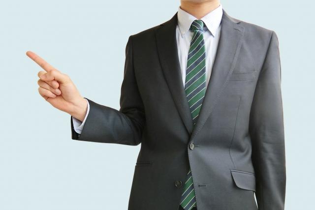 人差し指を立てたスーツの男性