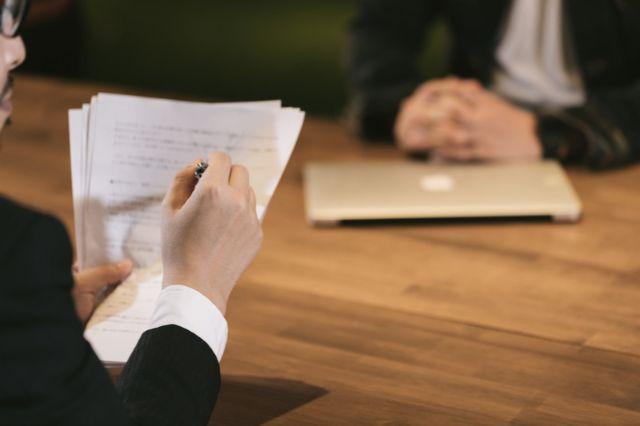 手に持った書類に書き込む男性