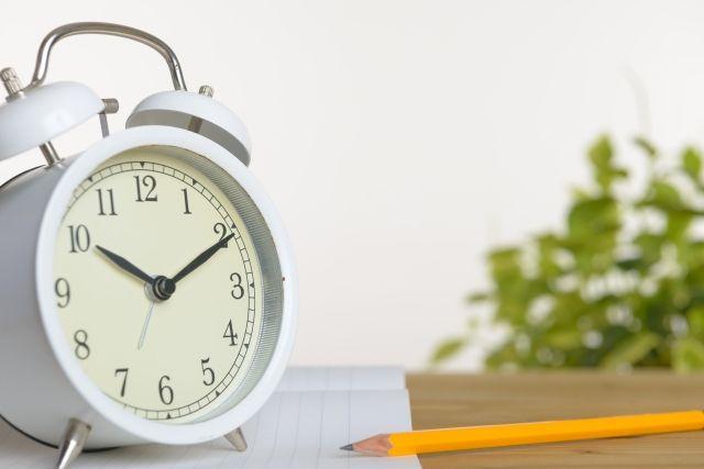机に置かれた時計と鉛筆