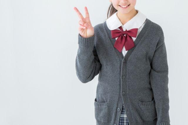 2本指を立てる笑顔の学生