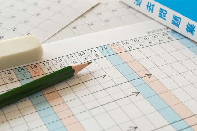 机に広げられたスケジュール表と鉛筆