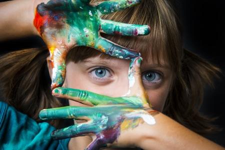 手にいろいろな色の絵の具を付けた外人の女の子の写真。450px×300pxサイズの画像の例として表示