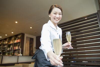 飲食店で働く女性の写真。ドリンクをお客さんに笑顔で渡すイメージ。.pngファイルとして保存された写真