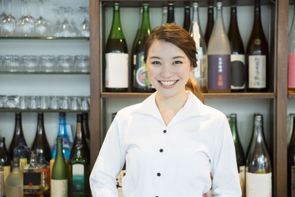 居酒屋の女性店員のイメージ画像。背後に一升瓶が並んでいる。お店の雰囲気は正しく伝わっていますか?と微笑みながらこちらに質問しているイメージ