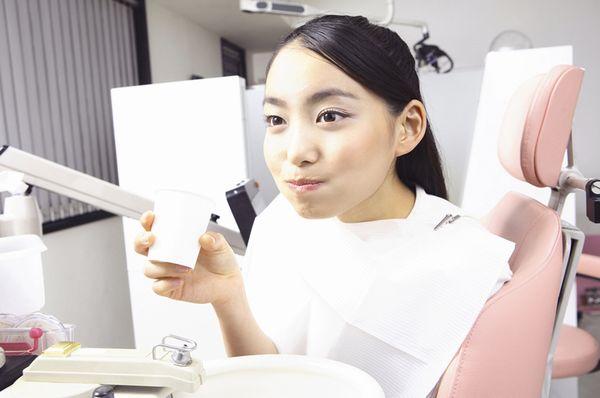 境界のはっきりしない.jpgで保存された写真画像の例として掲示。歯医者で口をゆすぐ若い女性の写真