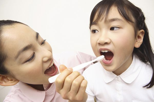 はみがきを小さい女の子に教えている、若い女性歯科衛生士