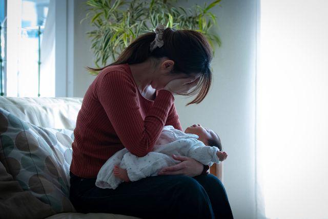 赤ちゃんを抱っこしながら頭を抱え込む女性