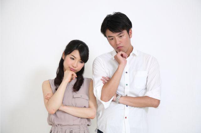顎に手を当て悩む男女