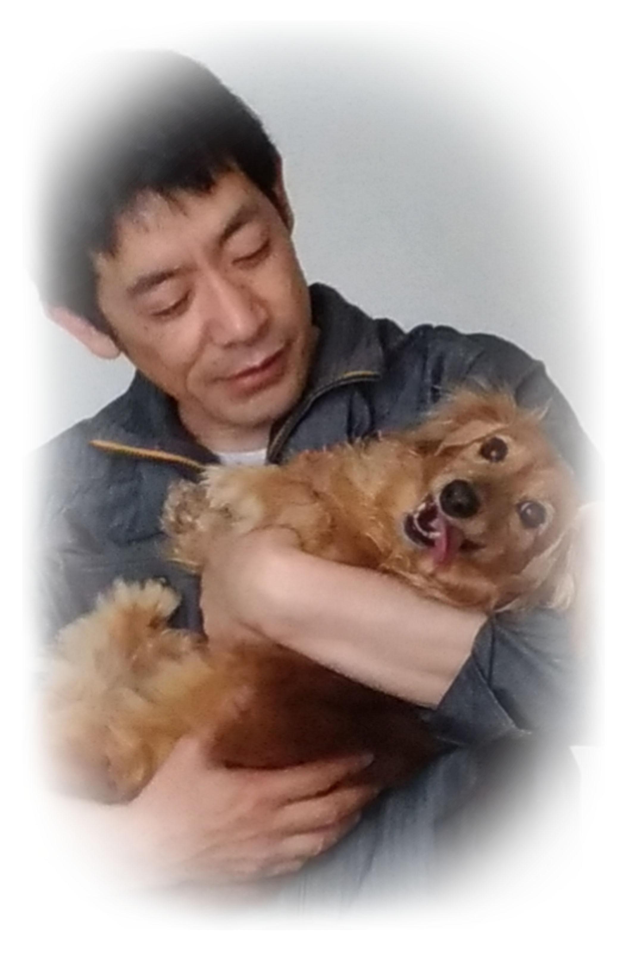 犬を抱っこしている店長