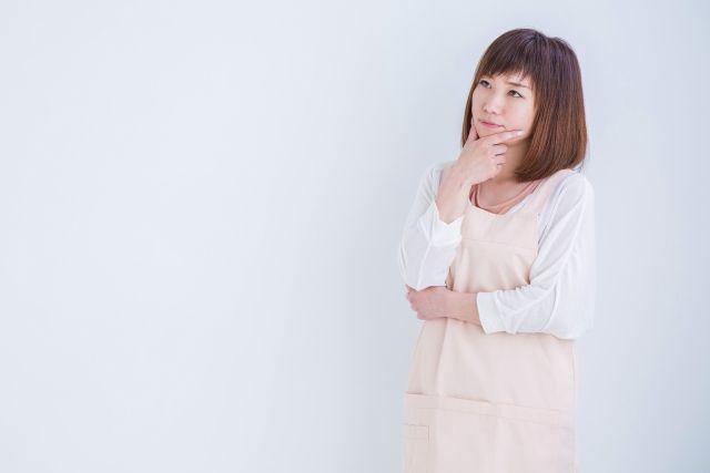 エプロン姿で悩む女性